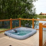 Golden Oak ballustrade with clear glass, stone deck boards and square hot tub