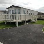 Cream Ballustrade wrap around deck with Stone deck boards and Hot Tub