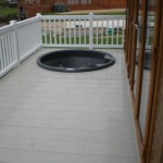 White ballustrade with stone deck boards with round hot tub